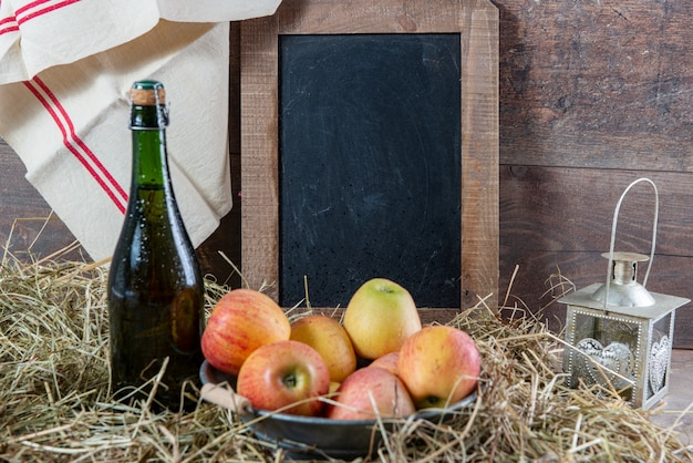 Bottle of cider with apples on the straw, and school chalkboard Premium Photo