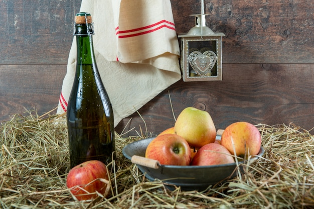 Bottle of cider with apples on the straw Premium Photo
