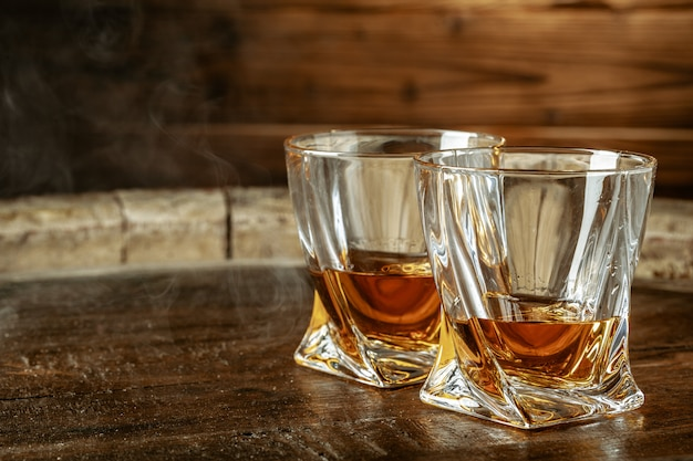 A bottle of cognac and glass on a brown wooden . brandy Premium Photo