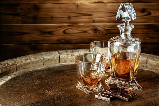 A bottle of cognac and glass on brown wooden. brandy Premium Photo