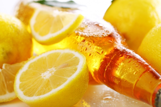 Bottle of cold beer with fresh lemons Free Photo