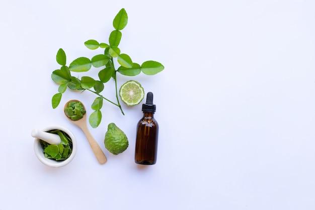 Bottle of essential oil and  fresh kaffir lime or bergamot fruit with leaves Premium Photo