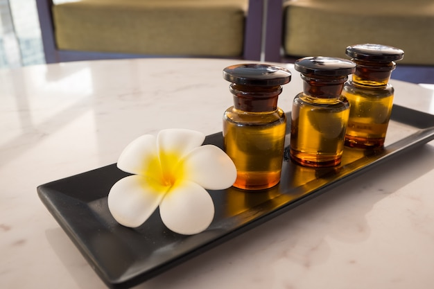 Bottle of essential oil and jasmin flower with plumeria flower setup on marble table. Premium Photo