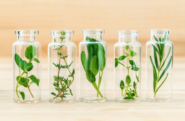 The bottle of essential oil with herbs on wooden background . Premium Photo