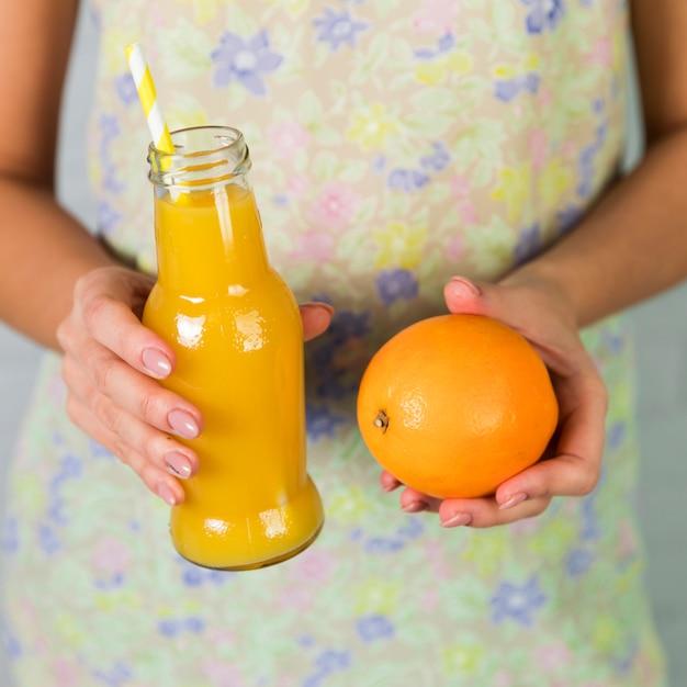 Bottiglia di succo d'arancia fresco e arancia Foto Gratuite