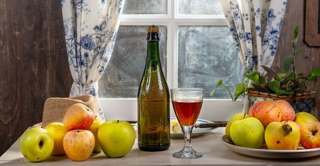 Bottle and glass of cider with apples. near the window, in rustic house Premium Photo