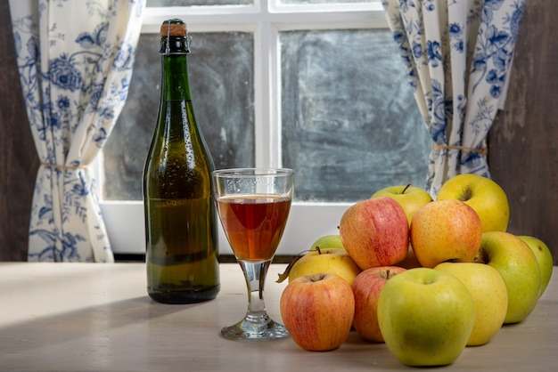 Bottle and glass of cider with apples. near the window, in the rustic house Premium Photo