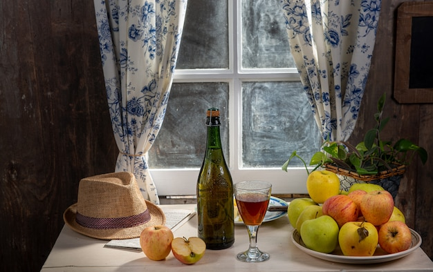 Bottle and glass of cider with apples. in rustic house Premium Photo