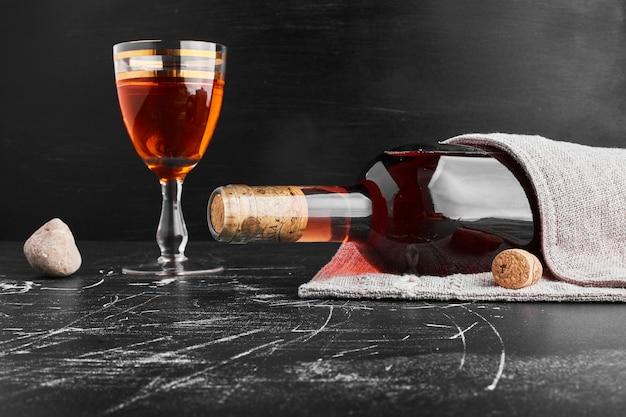 Una bottiglia e un bicchiere di vino rosato. Foto Gratuite
