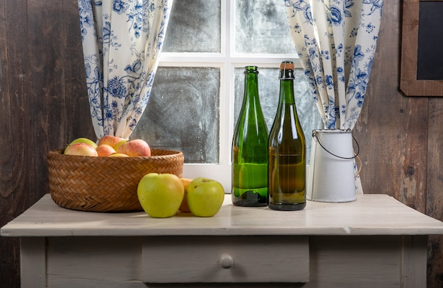 Bottle and glasses of cider with apples, near the window, in rustic house Premium Photo