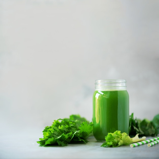 Bottle of green celery smoothie on grey concrete background with copy space Premium Photo