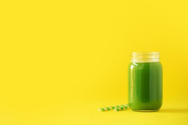Bottle of green celery smoothie on yellow background Premium Photo