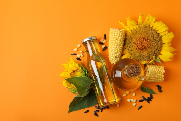 Bottle and jug of oil and ingredients on orange background Premium Photo