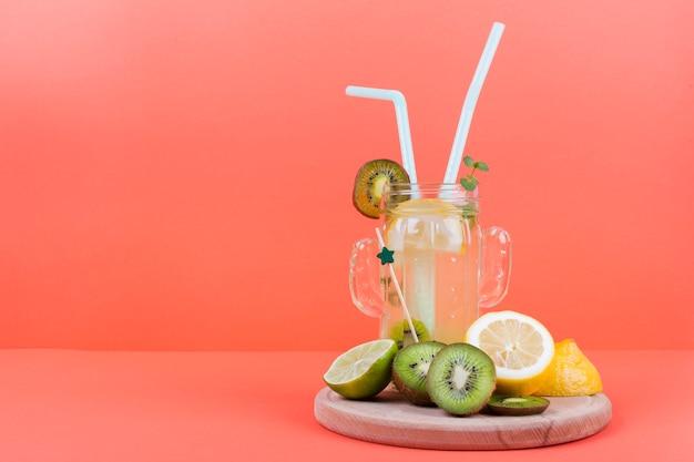 Bottle of lemonade with cut fruit Free Photo