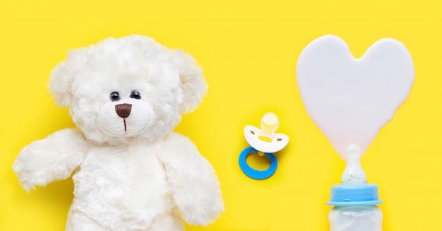 Bottle of milk for baby and baby pacifier with toy bear on yellow Premium Photo