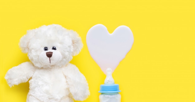 Bottle of milk for baby with toy white bear on blue background. Premium Photo