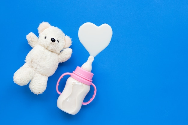 Bottle of milk for baby with toy white bear on blue Premium Photo