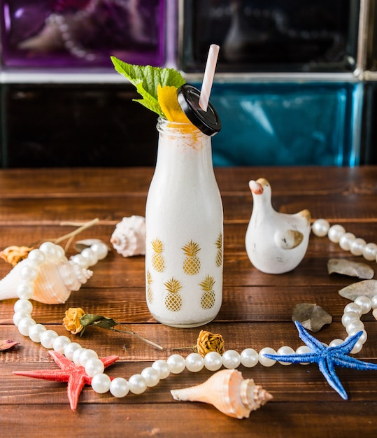 Bottle of milky shake with pipe and beach decors. Free Photo
