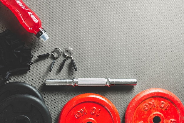 Bottle near parts of dumbbell Free Photo