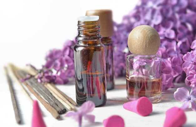 Бутылка эфирного масла и ладана с фиолетовым сиреневым цветком Premium Фотографии
