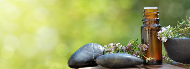 緑のボケの背景にラベンダーの花を持つテーブルにこぼれたエッセンシャルオイルのボトル Premium写真