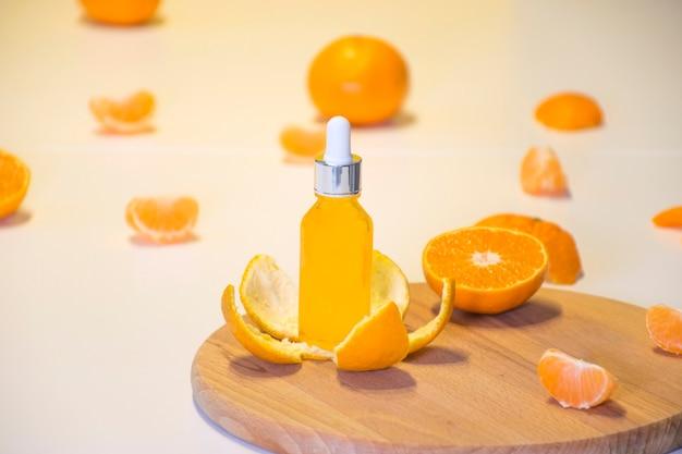 Бутылка органической био сыворотки с витамином с в кожуре мандарина с кусочками апельсина на белом фоне. Premium Фотографии