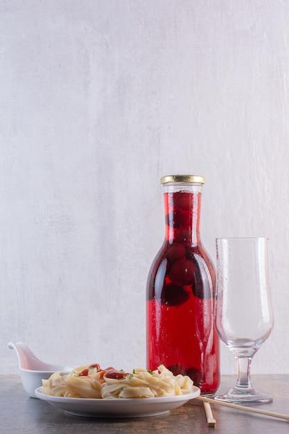 空のガラスと白い表面にパスタと赤いジュースのボトル 無料写真