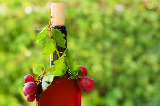 日当たりの良い緑の赤ワインのクローズアップのボトル Premium写真