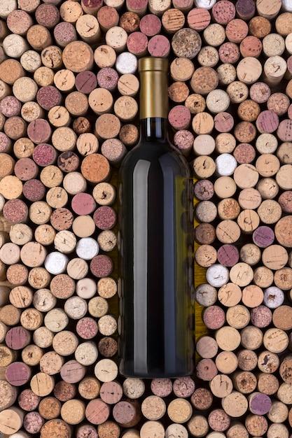 Бутылка белого вина и пробки на деревянном столе Premium Фотографии