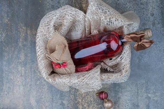 木製のバスケットにリボンで飾られたワインのボトル。高品質の写真 無料写真