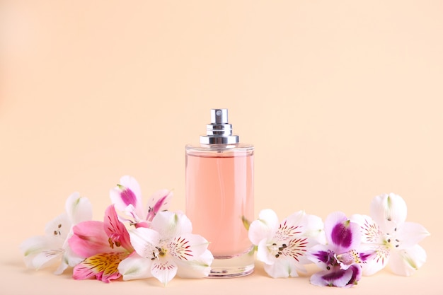 Bottle of perfume with flowers on beige Premium Photo