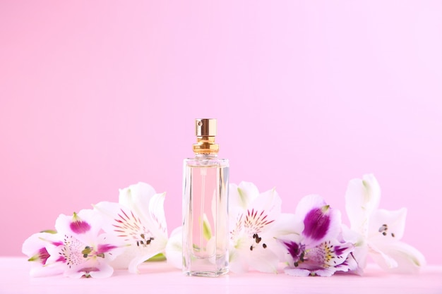 Bottle of perfume with flowers on pink Premium Photo