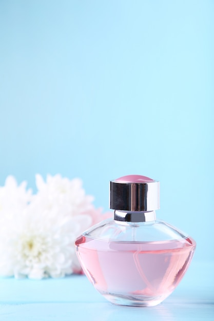 Bottle of perfume with white flowers on blue Premium Photo