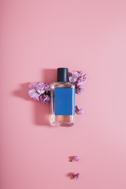 Bottle of perfumes on pink wall with flowers Free Photo