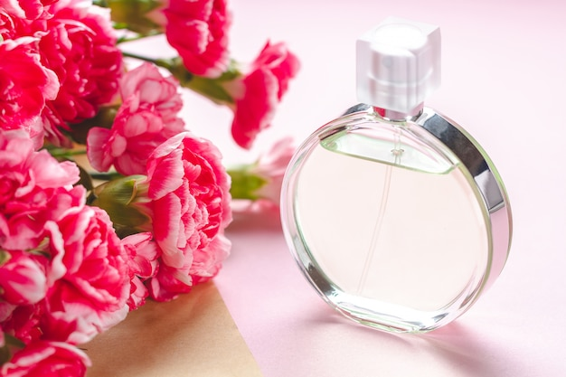 A bottle of person perfume and a bouquet of flowers on a pink surfce. give presents and flowers to person. receive gifts from loved people on holidays Premium Photo