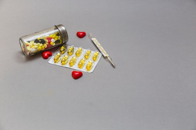 Bottle of pills; red heart and thermometer on grey background Free Photo