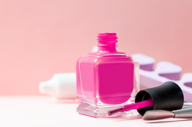 Bottle of pink nail polish and manicure tools on a table. Premium Photo