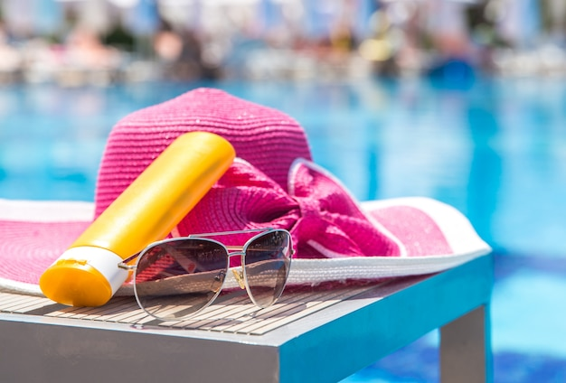 Bottle of sun cream, hat and sunglasses next to swimming pool in hotel Premium Photo
