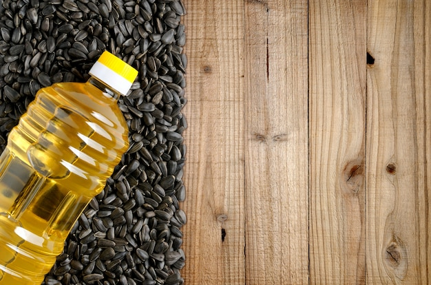 Bottle of sunflower oil and sunflower seeds on wooden Premium Photo