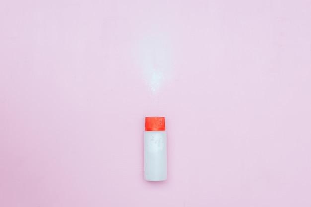 Bottle of talcum baby powder on pink background. powder spilled from white container Premium Photo