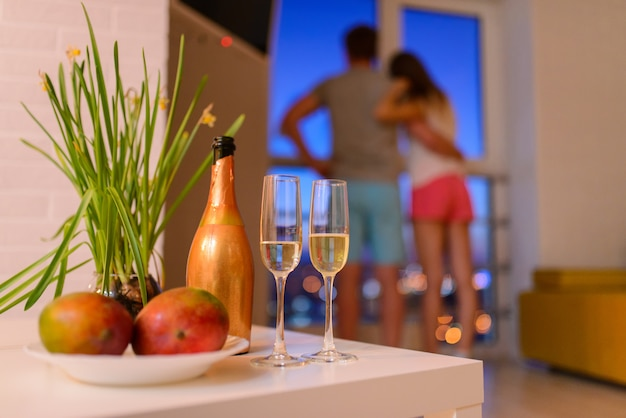 Bottle and two glasses of champagne on coffee table in living room Premium Photo