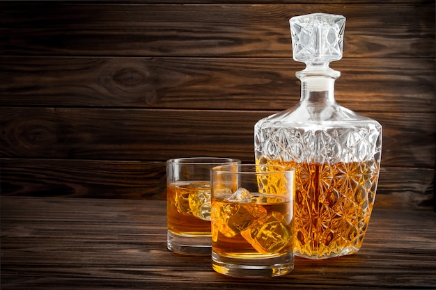 Bottle and two glasses with ice whiskey Premium Photo