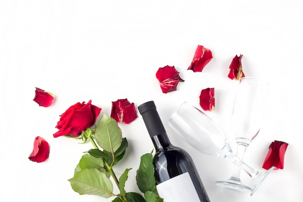 Bottle of wine, glasses and red roses Premium Photo