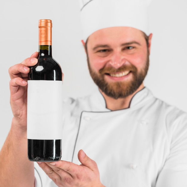 Bottle of wine in hands of chef cook Free Photo