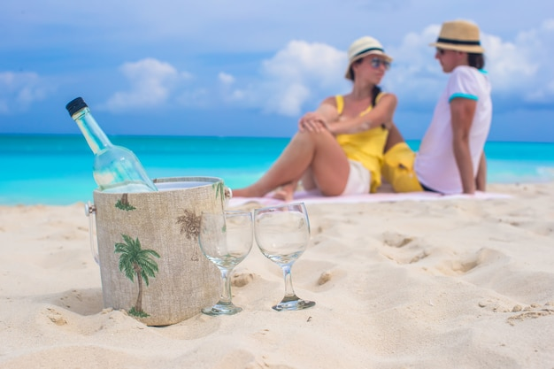 Bottle of wine and two glasses background happy couple at beach Premium Photo