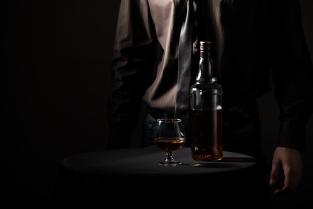 Bottle with an alcoholic drink and a glass Premium Photo