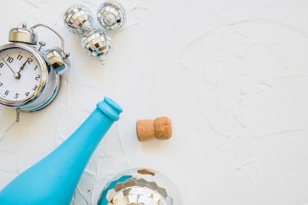 Bottle with clock and baubles on white table Free Photo