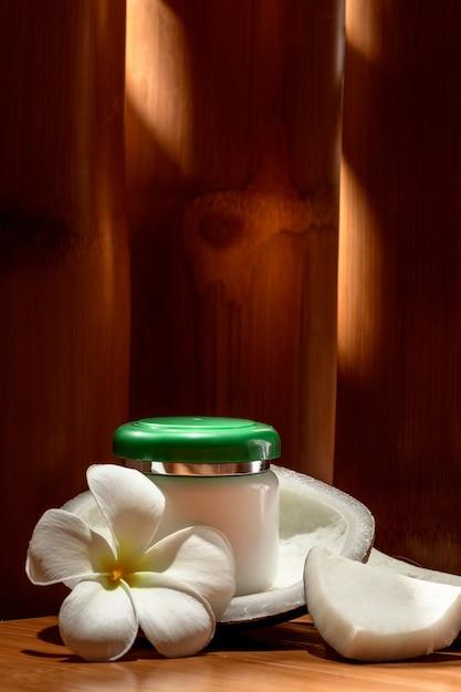 ココナッツとプルメリアの花を背景に化粧品、クリームのボトル。 Premium写真