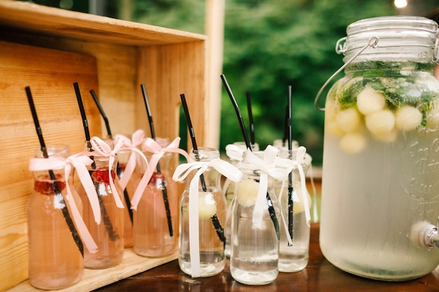 Bottle with fresh lemonade and glasses around it stands on the dinner table in the garden Free Photo