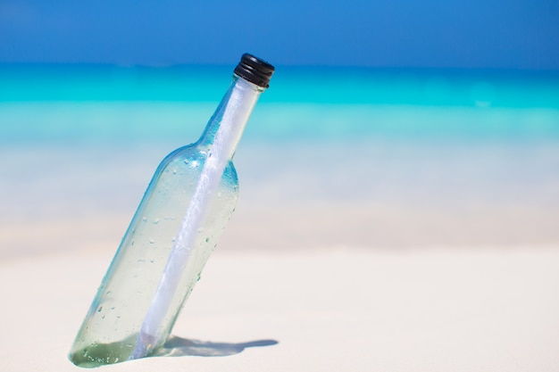 Bottle with a message buried in the white sand Premium Photo